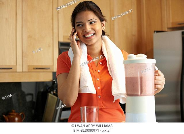 Mixed race woman in kitchen using blender