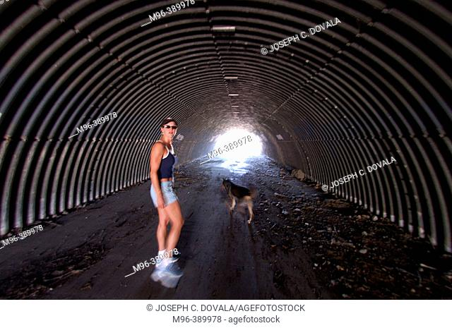 Woman and dog in culvert
