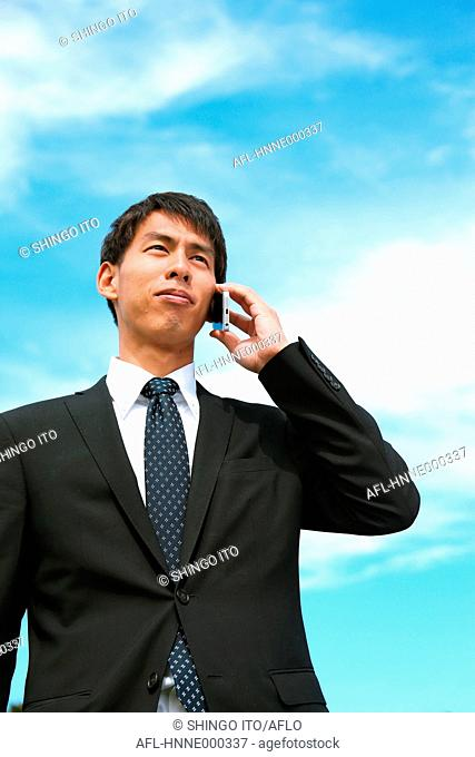 Young Japanese businessman on the phone
