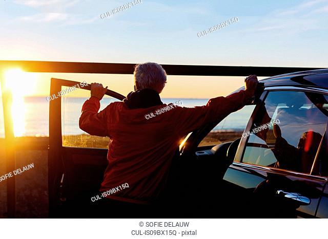 Senior man watching sunset beside car, Livorno, Italy
