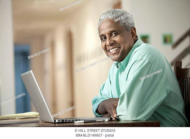 Smiling Black man sitting with laptop