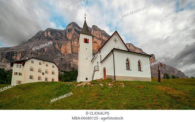 The church and the Hospice of Santa Croce in Alta Badia at the foot of the giant West face of Sasso della Croce, Dolomites, South Tyrol