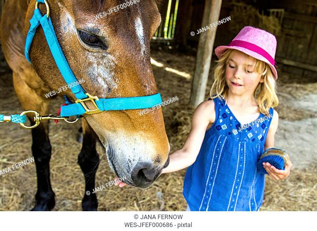 Greece, Corfu, Agios Georgios, little girl stroking horse