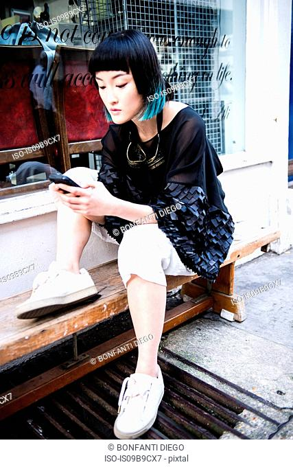 Young stylish woman waiting outside shop looking at smartphone