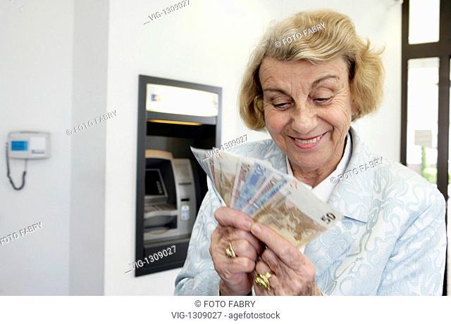 DEU GERMANY, ETTLINGEN, 03.04.2009, Seniorin am Bankautomat mit Geldscheinen| Elderly Person at cashpoint with banknotes - Ettlingen, Baden-Württe, DEU Germany