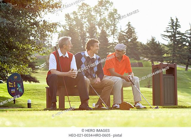 three golfers sitting on bench by tee box