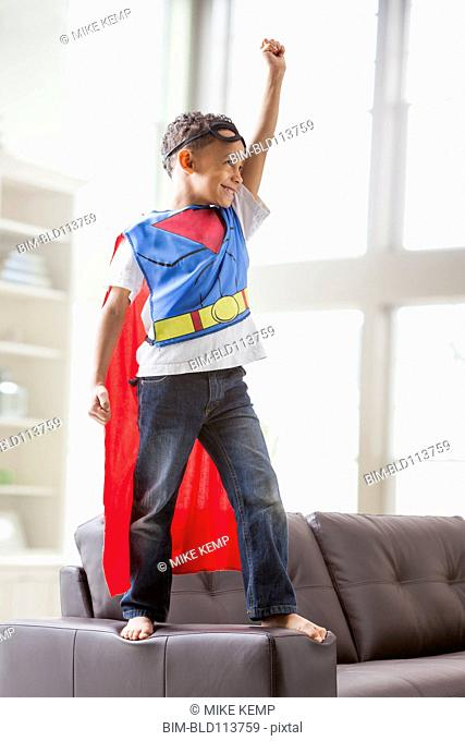 Mixed race boy playing superhero