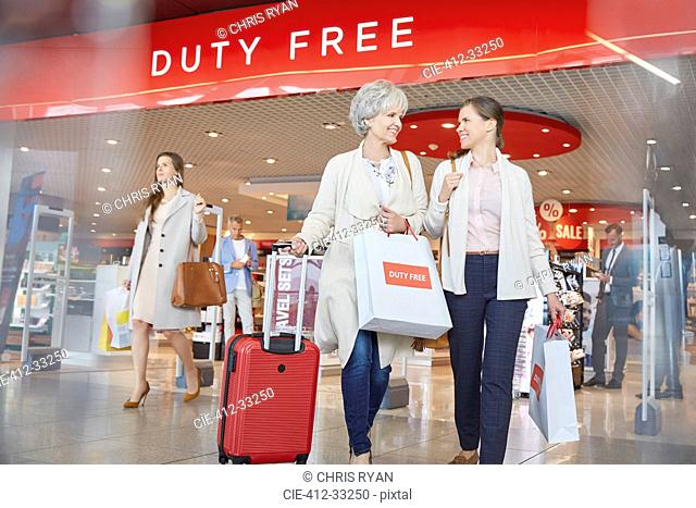 Women leaving airport duty free shop with shopping bags and suitcase