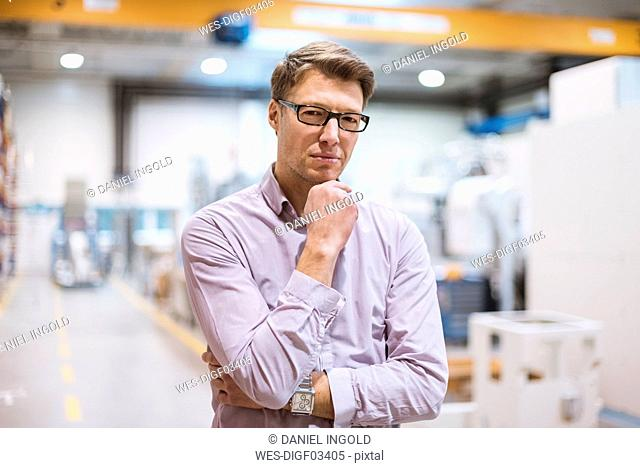 Portrait of serious businessman in factory