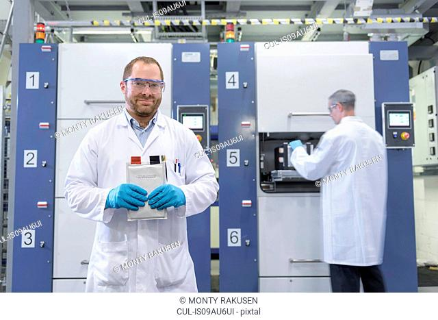 Scientist with lithium ion pouch cell manufacture machine in battery research facility, portrait