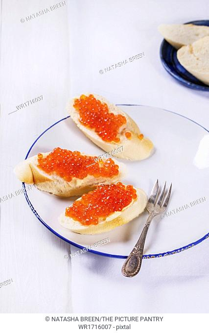 Sandwiches with red caviar on white plate, served with vintage fork over white table