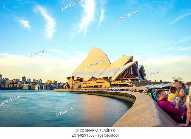 SYDNEY, AUSTRALIA - APRIL 21: Long exposure of people passing by the Opera bar next to Sydney Opera house. April 2016