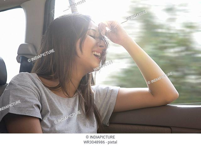 Young women in car hair gets blown by the wind