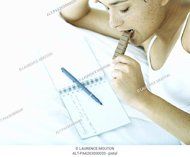 Woman lying on side on bed eating chocolate and looking down at notebook with pen lying across it
