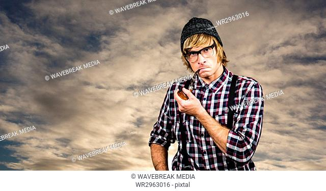 Confident hipster smoking pipe against sky