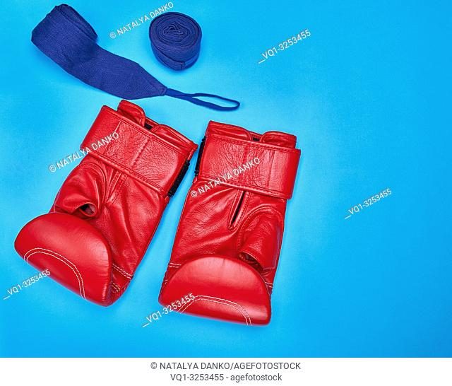 pair of red leather boxing gloves and a textile bandage on a blue background, copy space
