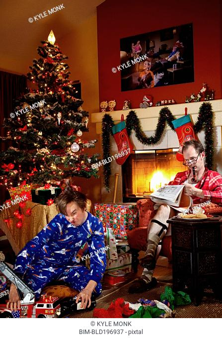 Caucasian father and son in living room on Christmas morning