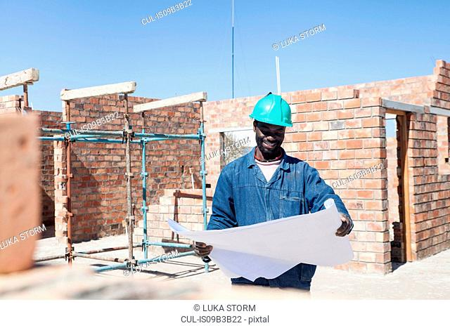 Builder looking at blueprint on construction site