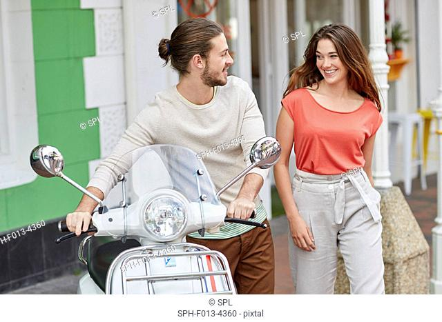 MODEL RELEASED. Young couple outside cafe, man holding moped