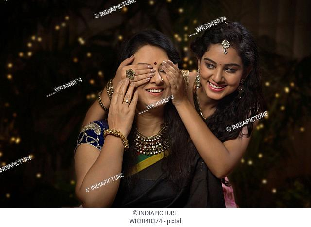 Young girl closing her mother's eyes on diwali
