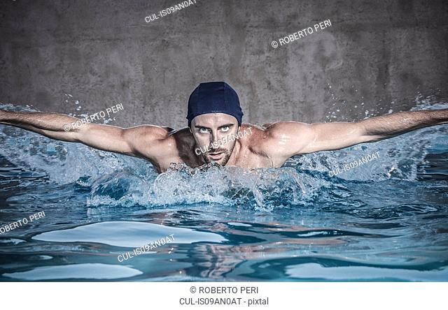 Portrait of mid adult man doing butterfly stroke in swimming pool, Cagliari, Sardinia, Italy