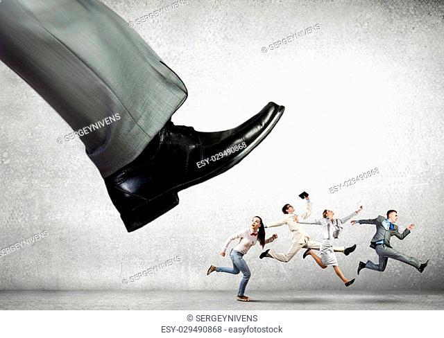Big businessman foot kicking businesspeople running away