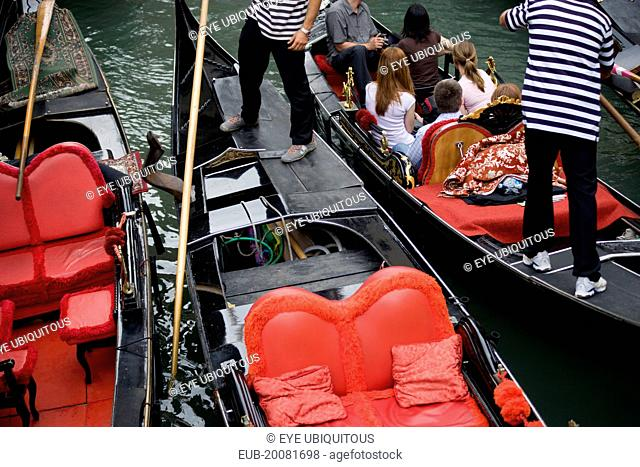 Gondolas with tourists passing each other closely in the narrow canals in the San Marco district