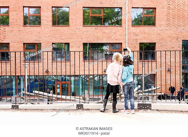 Girls (8-9) taking selfie by school