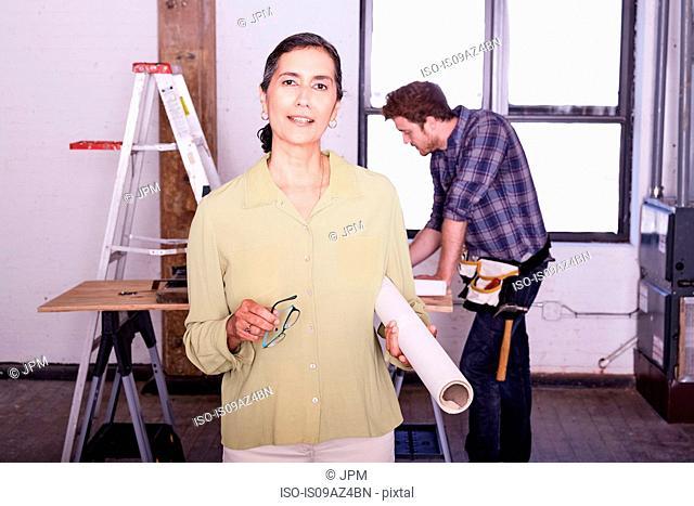 Woman holding blueprint looking at camera smiling