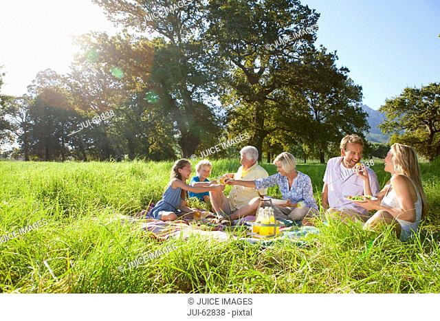 Multi-generation family having picnic in rural field