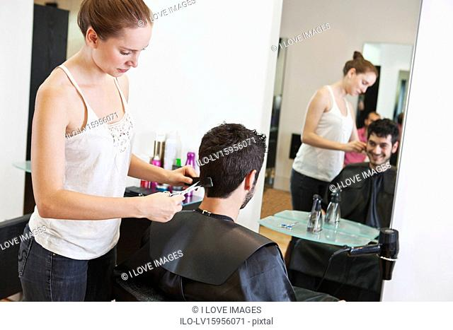 A female hairdresser cutting his male clients hair with scissors