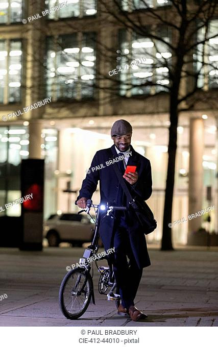 Businessman with bicycle using smart phone on urban sidewalk at night