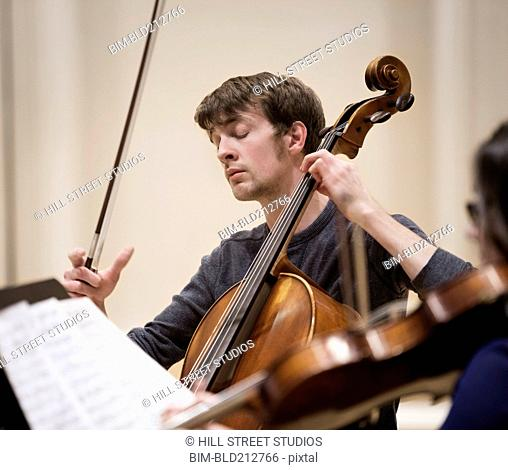Caucasian student playing cello in string quartet