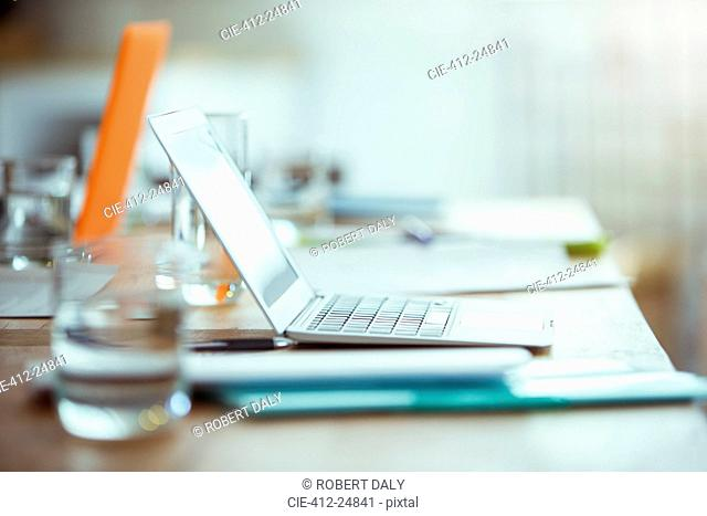 Office supplies, laptop and glass of water on desk in office