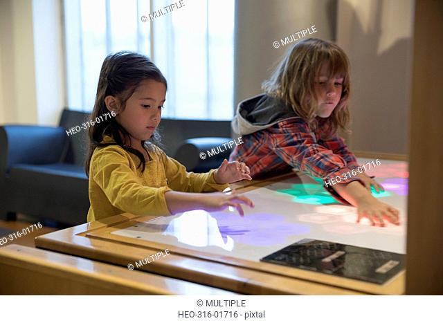 Boy and girl playing with touch screen light display in science center