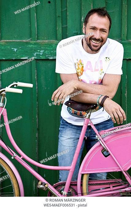 Germany, Bavaria, Portrait of mature man leaning on pink bicycle, smiling
