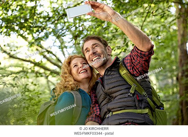 Hiking couple taking selfies with smart phone in forest