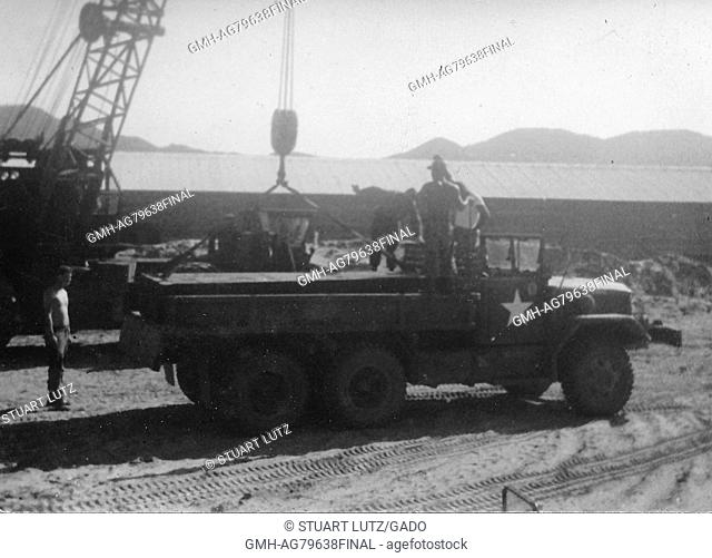 A photograph of several United States Army serviceman unloading building supplies from an M35 military truck, other building materials are located near the...