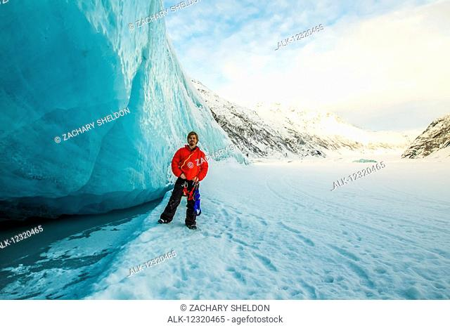 A man stands besides an iceberg from the Valdez Glacier, Valdez, Southcentral Alaska, USA