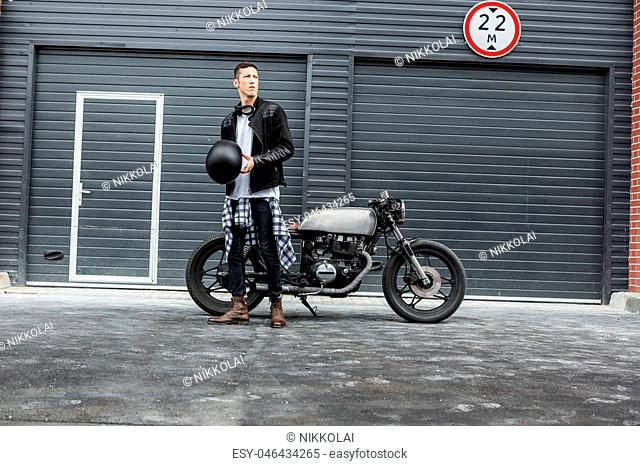 Handsome rider biker man hold his black helmet near industrial gates and classic style cafe racer motorcycle. Bike custom made in vintage garage