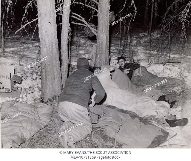 Scouts belonging to A W R Burrows' troop in winter camp, Canada, bedding down for the night in the open air