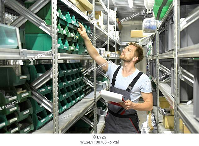 Man in warehouse looking in box