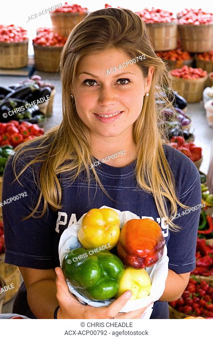 Jean Talon Market with young woman displaying produce, Montreal, Quebec, Canada