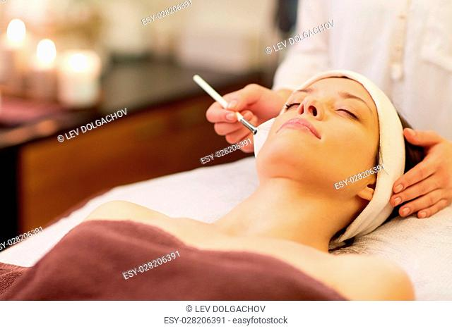 people, beauty, cosmetology and treatment concept - close up of beautiful young woman lying with closed eyes and cosmetologist applying facial mask by brush at...