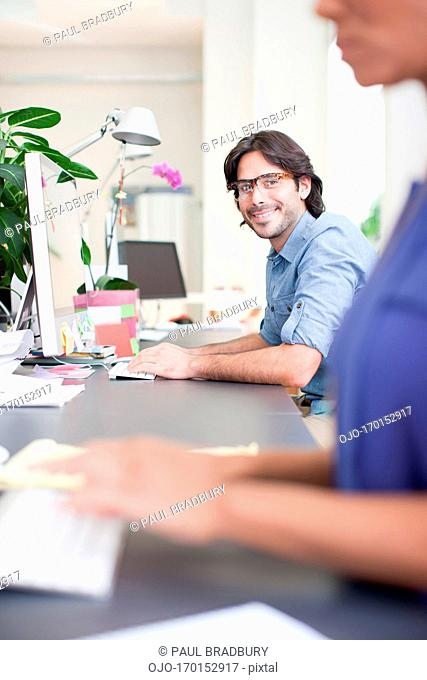 Portrait of smiling businessman at computer in office