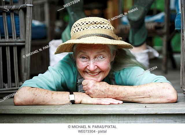 Senior woman with straw hat laying on stomach looking into camera smiling