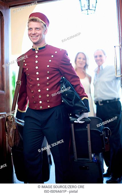 Bellhop carrying luggage in hotel