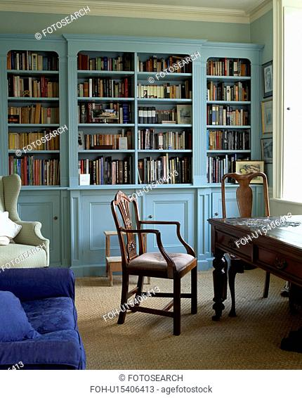 Antique desk and chair in traditional study with pale blue bookcase