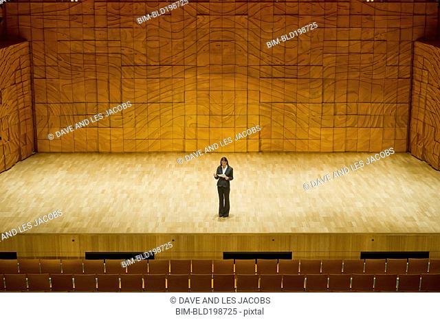 Hispanic businesswoman practicing speech in empty auditorium