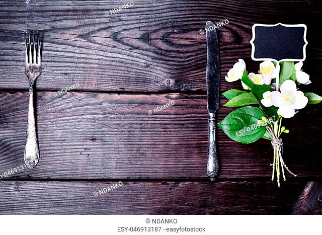 Iron fork and knife with a bouquet of jasmine on a brown wooden background, empty space in the middle